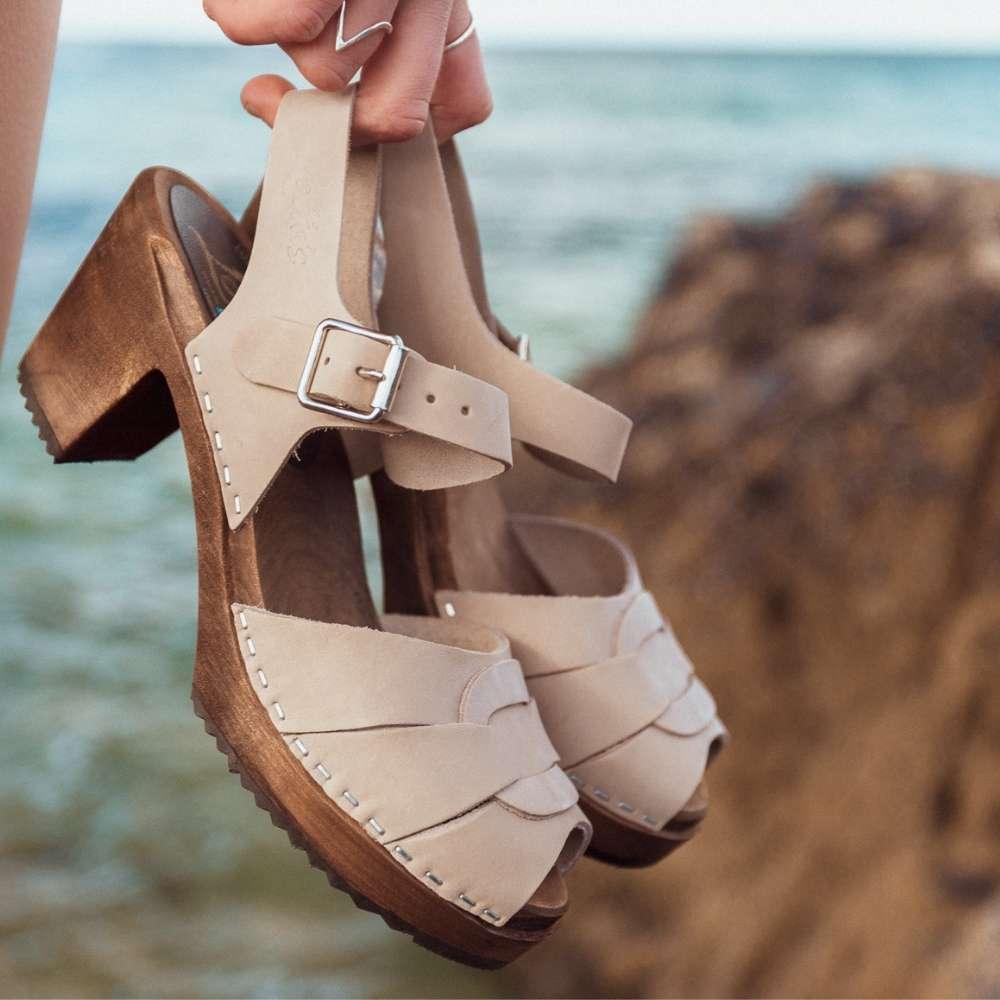 Sea grey clogs on the beach